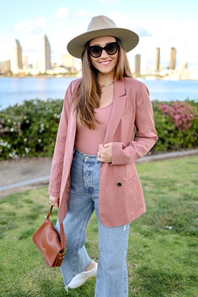 girl wearing pink blazer in front of san diego skyline