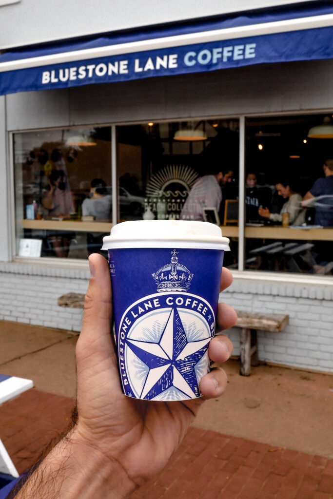 blue stone lane coffee cup in front of store in montauk