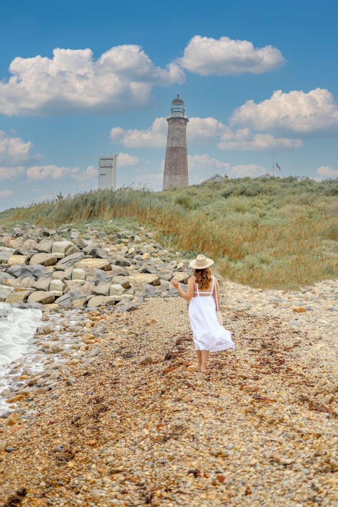 girl on beach in front of montauk lighthouse