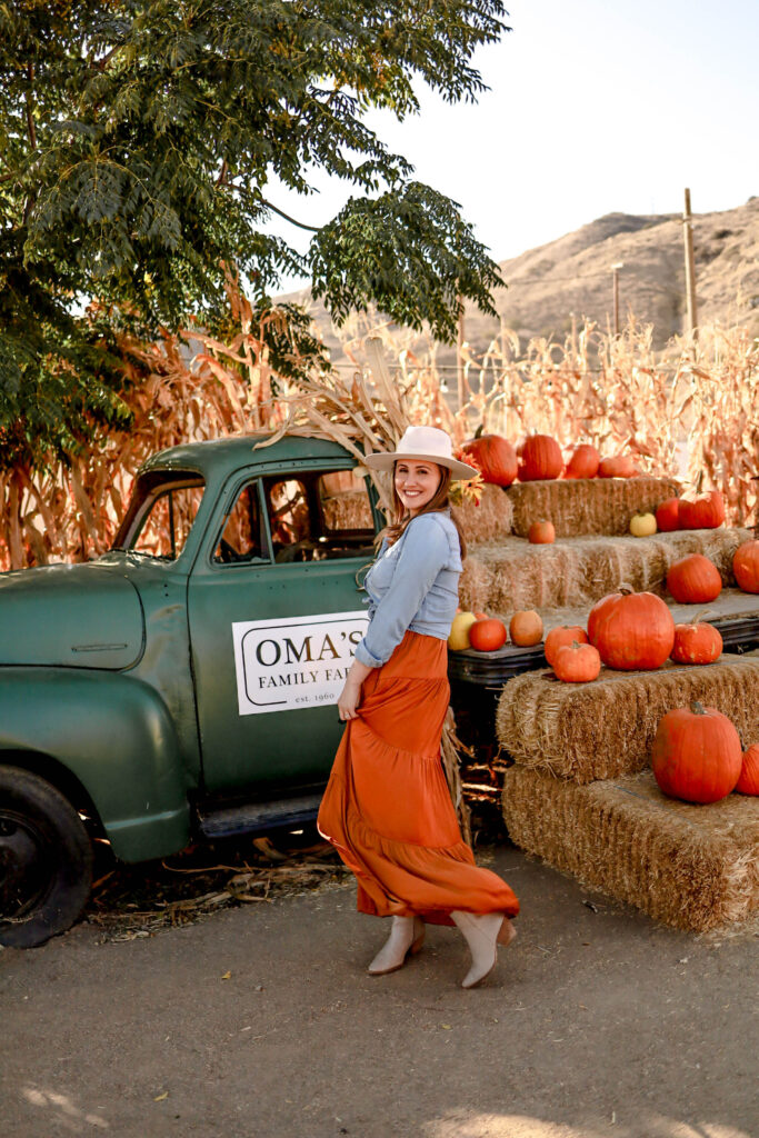 Girl in front of green truck with fall decor at Oma's Pumpkin patch